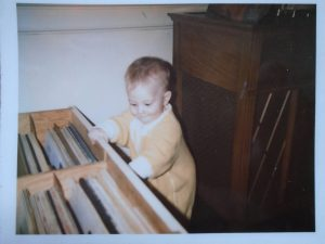 Me as a baby looking at a drawer full of music records.